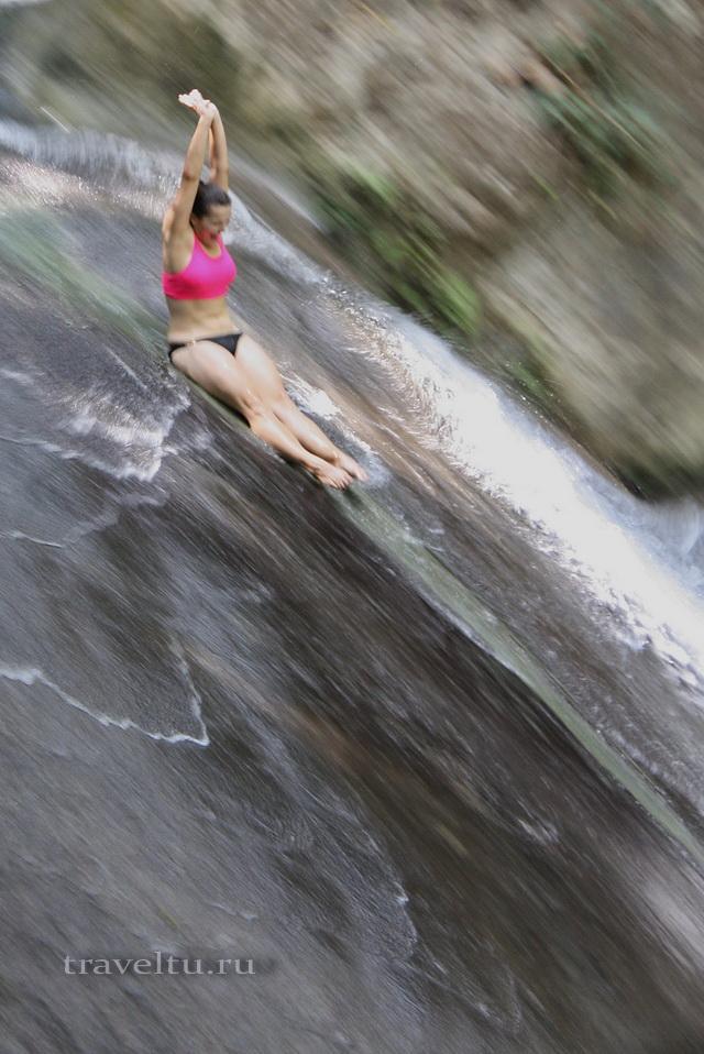 Водопад Эраван. Таиланд. Девушка катится по водопаду