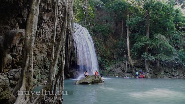 Мальчик у водопада сидит на камне