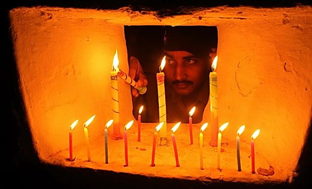 Индийский солдат зажигает праздничные огни