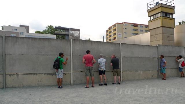 Люди смотрят в щели между плитами