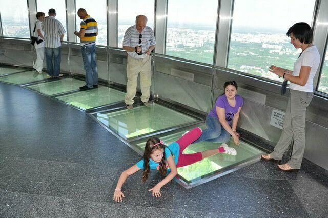 Люди на смотровой площадке смотрят на город через стеклянный пол.